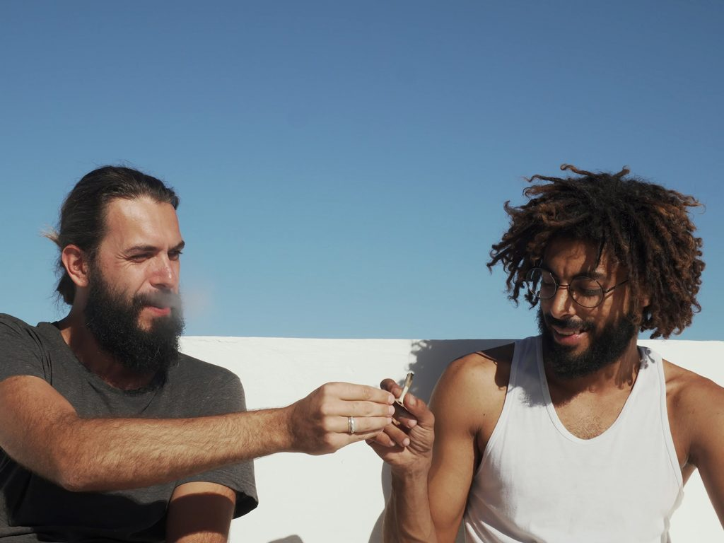 Two men smoking cannabis on a sunny day